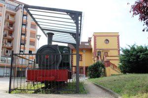 Locomotora de vapor SHE 11, al fondo la Antigua Estación del Ferrocarril Vasco Asturiana